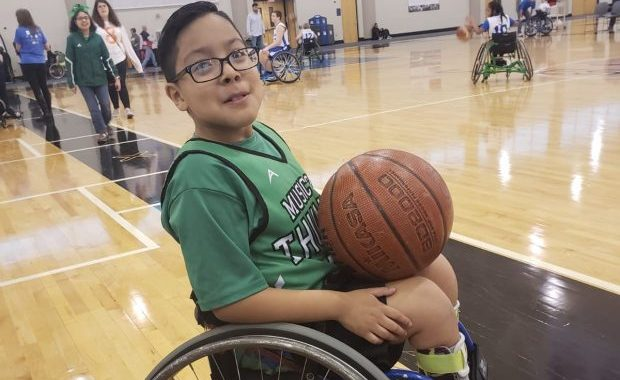 Chuy sitting in his wheelchair on a basketball court holding a basketball