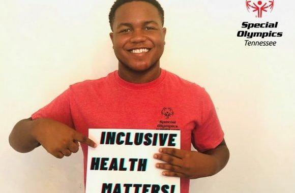 """Special Olympian, Eric Massey, holds sign that says, """"Inclusive Health Matters!"""""""