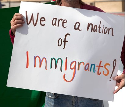Image of person holding sign that says We are a nation of immigrants