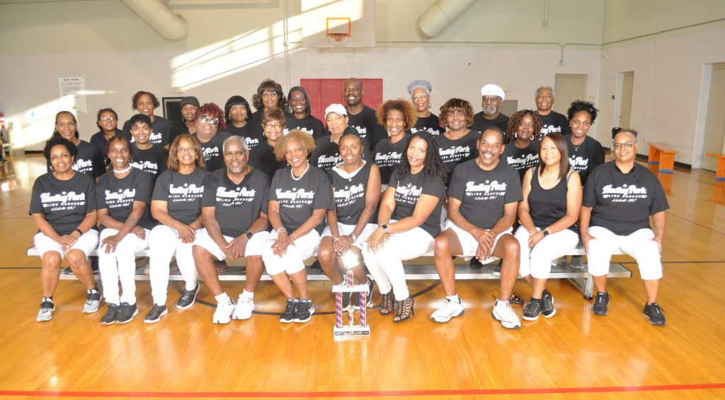 Hadley Park Line Dancers in a seated group photo wearing black and white t-shirts with the Hadley Park Line Dancers logo on the shirt. A large trophy is standing on the gymnasium floor in front of them.