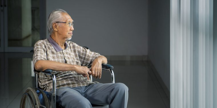 Older adult sitting in a wheelchair looking out a window.
