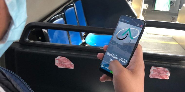 Image of person riding a bus, holding a cell phone in hand with the ABLELink logo on the screen.