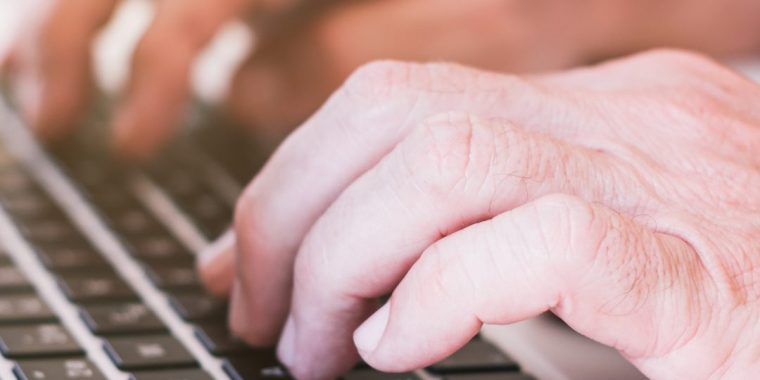 Image of a person's fingers on laptop keyboard.